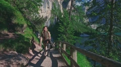 Woman hiker walking around the Braies lake and enjoys his spectacular sceneries Stock Footage