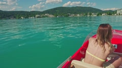 Beautiful woman driving a motor boat on Worthersee lake, Pörtschach am Stock Footage