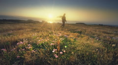 Mature middle aged woman hiking field of wildflowers on Oregon Coast at sunset Stock Footage