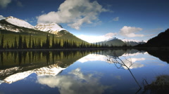 Lake reflecting mountain, forest and sky Stock Footage