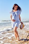 Pregnant woman in blue tunic seashore walk - stock photo