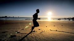 Teen boy jogging on Pacific Beach at sunset Stock Footage