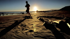 Teen boy jogging on Pacific Beach at sunset - stock footage