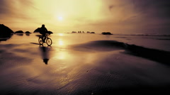 Young man riding mountain bike on Pacific beach at sunset Stock Footage