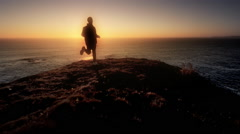 Young man jogging trail overlooking Pacific Ocean at sunset Stock Footage