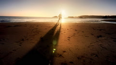 Young couple running on Pacific beach at sunset - stock footage