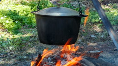 smoked tourist pot over camp fire. man stirs food ladle - stock footage