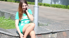 Young wooman beautiful lovely girl speaks on her cell phone with friends while Stock Footage