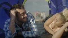 4K Young couple in tent at the beach relaxing while friends have fun outside Stock Footage