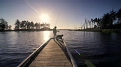 Senior man and his dog fly fishing off dock, Oregon Stock Footage
