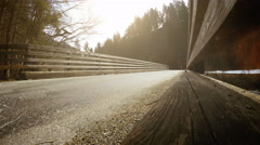 Auto moves over village bridge - wide angle view Stock Footage