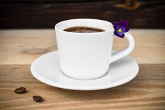 Cup of espresso with coffee beans on wooden table Stock Photos