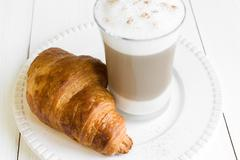 Croissant and glass of latte macchiato on white plate - stock photo