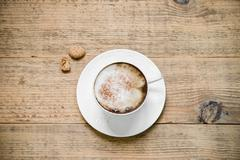 Cup of cappuccino with biscotti on woode table Stock Photos
