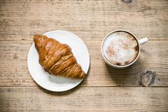 Cup of cafe latte and croissant on wooden table - stock photo