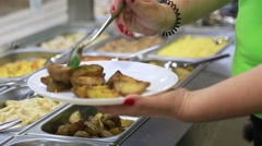 Chef puts fried potatoes on a white plate in cafe Stock Footage