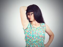 Young woman, smelling, sniffing her wet armpit, something stinks Stock Photos