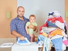 Caucasian man father and son in his hands, ironed clothes in the room near th Stock Photos
