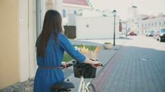 Back view of a girl walking her bike with flowers and bread in the basket Stock Footage