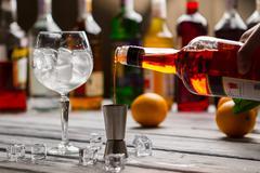 Bottle pours liquid into jigger. Stock Photos