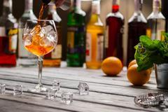 Jigger pours liquid into wineglass. Stock Photos