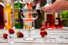 Red cocktail pours through sieve. Stock Photos