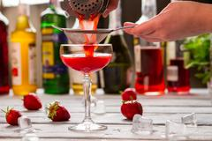 Red drink pours through sieve. Stock Photos
