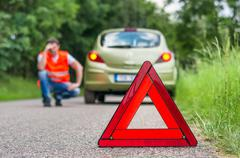 Broken car on the road and unhappy driver with red warning triangle Kuvituskuvat