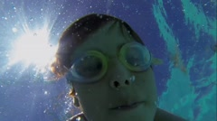 Face of young boy in glasses which swims among bubbles Stock Footage