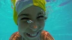 Young girl swims under pool water at summer sunny day Stock Footage
