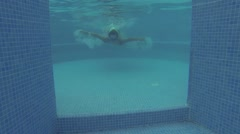 Young boy in glasses swims under water of pool at summer Stock Footage