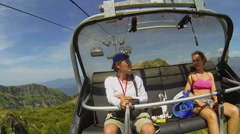 Couple ride on chair of ropeway in mountains at summer Stock Footage
