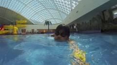 Man in glasses makes selfie during swim at pool of aquapark. Stock Footage