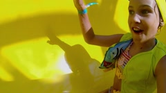 Little girl makes selfie during slides by yellow tube to water Stock Footage