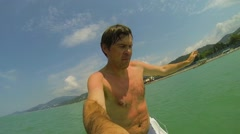 Man jumps into sea from vessel at summer sunny day Stock Footage