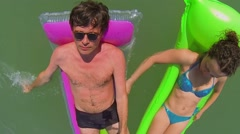 Husband and wife swim on inflatable rafts in sea at summer Stock Footage