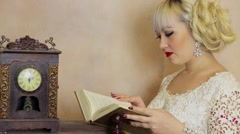 Woman with blond hair reads book near retro clock with pendulum Stock Footage