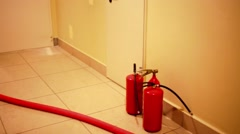Fire extinguishers and red hose on wet floor during accident Stock Footage