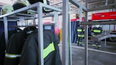 Garage with fireproof suits and firemen near walk truck Stock Footage
