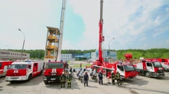 Fire-post with firemen stand near trucks at sunny day Stock Footage