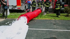 Firemen watch foam which goes from huge hose at fire-post Stock Footage