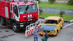 People make report of fire truck which moves old yellow car Stock Footage