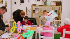 People with kids create art objects in small room Stock Footage