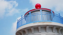Facade of top of tower in shape of lighthouse against sky with clouds Stock Footage