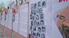 Memorial board with photos of WWII heroes in park at sunny day Stock Footage
