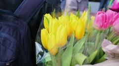 Woman holds two bouquets of yellow and pink tulips Stock Footage