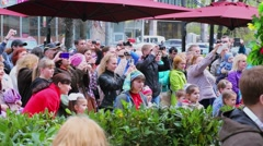 Crowd of people watch performance on street at spring sunny day Stock Footage