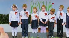 Children in military hats and WWII ribbons on stage during spring event Stock Footage