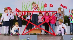 Children hold red ribbon in form of star on stage Stock Footage