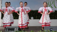 Six girls dance on stage in red-white country dresses Stock Footage